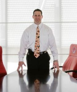 Gene Chizik poses in front of Bobby Lowder's chair at the AU Board of Trustees conference table.